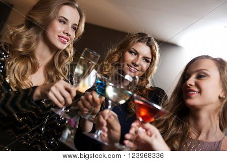 celebration, friends, bachelorette party and holidays concept - happy women drinking champagne and cocktails at night club bar