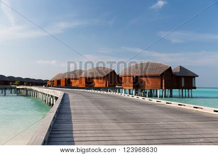 travel, tourism, vacation and summer holidays concept - bungalow huts in sea water on exotic resort beach