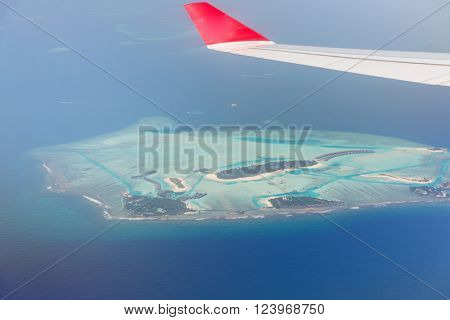 travel, summer vacation, transportation, air transport and vehicle concept - close up of airplane wing flying above Maldive island in ocean