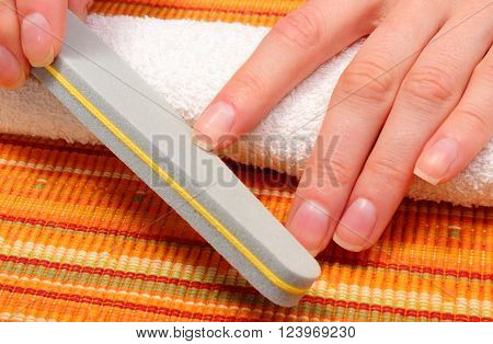Woman polishing fingernails with nail file filing nails care of hands and manicure