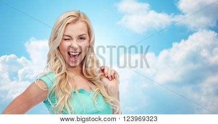 emotions, expressions, hairstyle and people concept - smiling young woman or teenage girl holding her strand of hair and winking over blue sky and clouds background