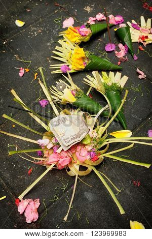 Balinese-Hindu offerings of flower petals money incense and rice are left in palm-leaf boxes for the Gods at a Hindu temple in Sebatu Sacred Springs Bali Indonesia.