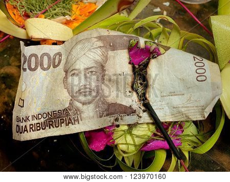 A stick of incense burns through an Indonesian banknote among Balinese-Hindu offerings of flower petals rice and cash on an altar at a Hindu temple at Sebatu Sacred Springs in Bali Indonesia.