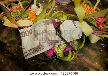 A stick of incense burns through an Indonesian banknote among Balinese-Hindu offerings of flower petals rice and money on an altar at a Hindu temple at Sebatu Sacred Springs in Bali Indonesia.