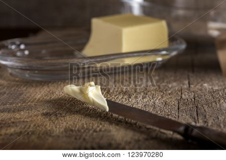 Knife with butter and butter dish in background ** Note: Shallow depth of field