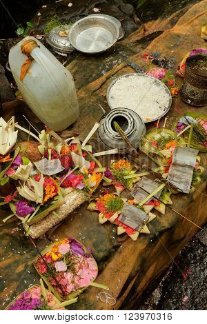Balinese-Hindu offerings of flower petals holy water rice money and incense are left for the Gods at a Hindu temple at Sebatu Sacred Springs in Bali Indonesia.