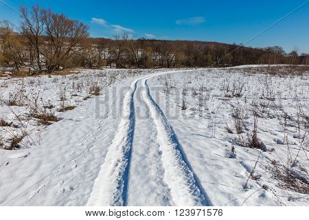 Snow track in the field at spring day