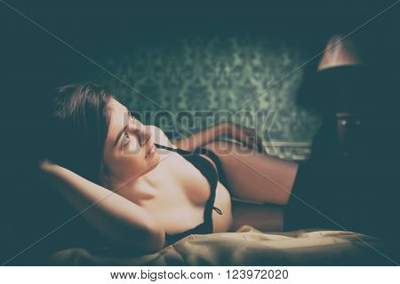 Sensual brunette in bed on green vintage background. Sexuality and sensuality. Boudoir and beauty