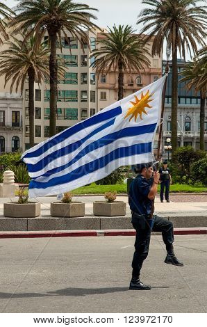 Montevideo, Uruguay - December 15, 2012: Police officer marching with flag at the Parade in Montevideo, Uruguay.