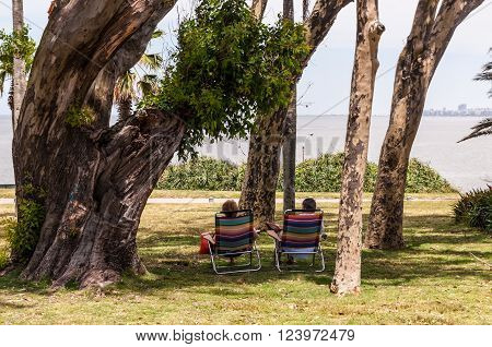 Montevideo, Uruguay - December 15, 2012: Unrecognizable couple sitting in the park, enjoying the sun, sea air and shadow in Montevideo, Uruguay.