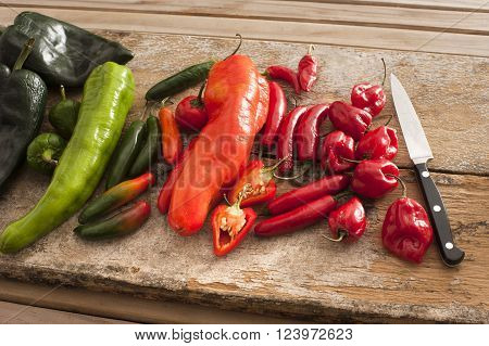 Assortment of colorful fresh red and green spicy chili peppers on an old rustic wooden table with a kitchen knife