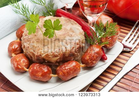 Traditional Russian food. Aspic meat jelly and smoked sausages.