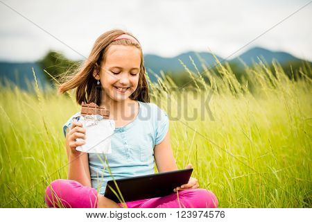Child eating and relishing chocolate while watching tablet - outdoor in nature