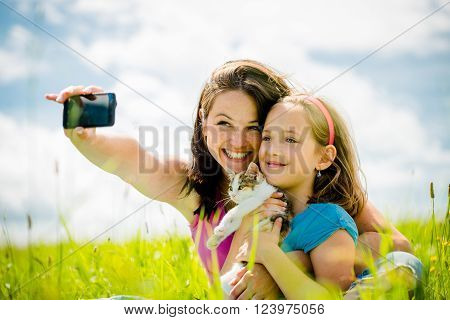 Young woman taking photo with her smart-phone camera of herself, her daughter and kitten