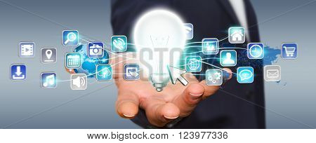 Businessman Holding Lightbulb With Digital Icons