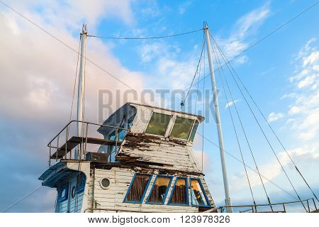 Close-up of a superstructure and the captain's cabin of the old weathered ship on a blue sky background.