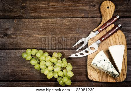 Two kinds of cheese and stainless steel cheese knife and fork with wood handle are is lying on the board of olive wood. Grapes are lying on a wooden board.