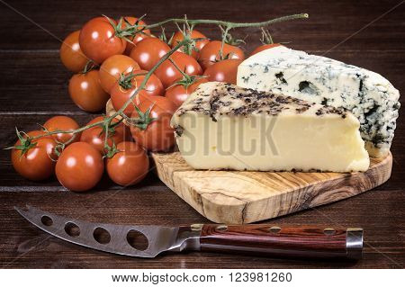 Two kinds of cheese and cherry tomatoes are lying on the board of olive wood. Stainless steel cheese knife with wood handle is lying on a wooden board in foreground. Photo is edited as an vintage with dark edges.