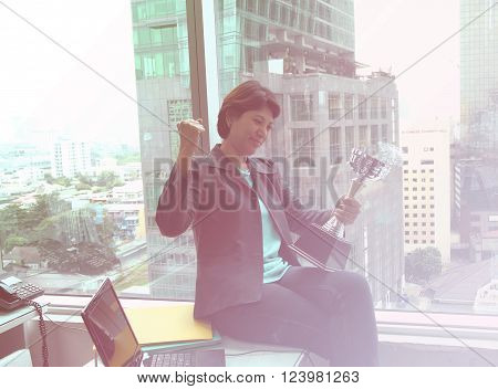 portrait of businesswoman keeping gold cup office Building background. Concept of victory and success