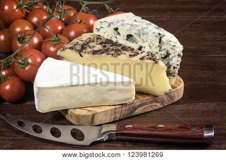 Three kinds of cheese and cherry tomatoes are lying on the board of olive wood. Stainless steel cheese knife with wood handle is lying on a wooden board in foreground. Photo is edited as an vintage with dark edges.