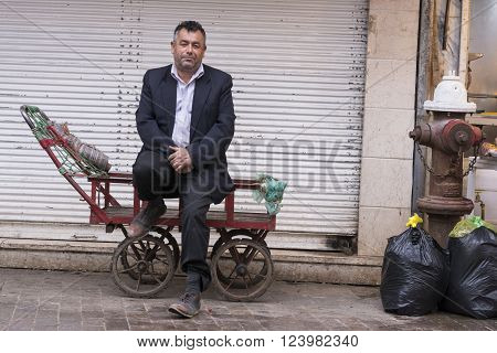 Gilan Province- Rasht IRAN-March 26 2016- Daily Bazaar Carter Man Sitting on His Cart in Front of Store Blind
