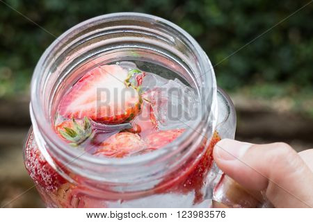 Hand hold glass of iced strawberry soda drink stock photo
