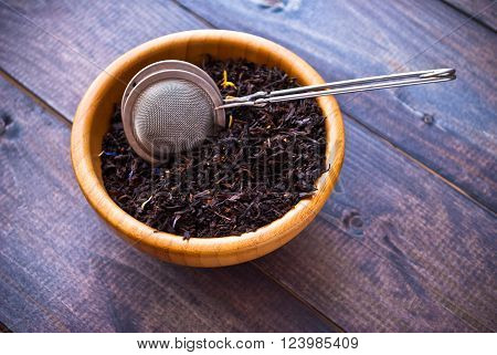 Dried tea leaves in bamboo bowl and tea strainer on shabby wooden background