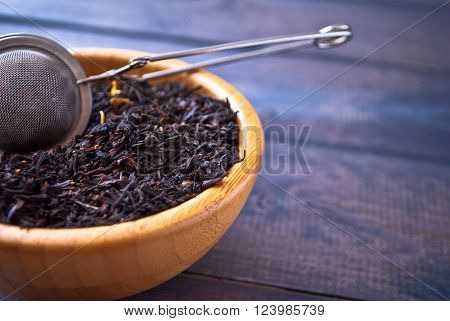 Dried tea leaves and flowers in bamboo bowl and tea strainer on wooden background