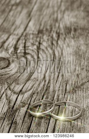 male and female wedding rings in gold with multicolor glare on an old cracked wooden board. selective focus