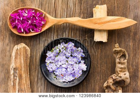 purple flower petals plants dead-nettle in a wooden spoon and pale blue flowers Persian speedwell on an old wooden board in the cracks close up. view from above. aromatherapy herbal tea homeopathic medicine
