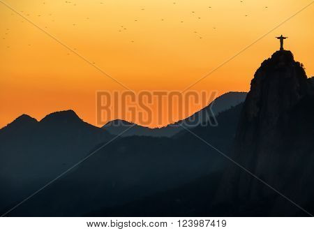 Rio De Janeiro, Brazil - August 31, 2015: Iconic, religious Christ Redeemer stature atop a mountain with a flock of birds