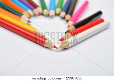 Close Up Picture Of Colored Pencil Crayons Arranged Inshape Of Heart On White Background. Assortment