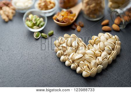 Pistachio nuts forming a heart-shape on slate background