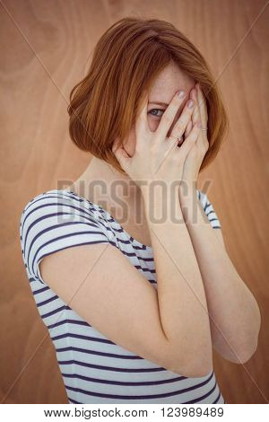beautiful hipster woman hiding her face on a wooden background