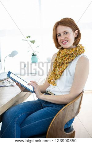 smiling hipster woman on a tablet at her desk