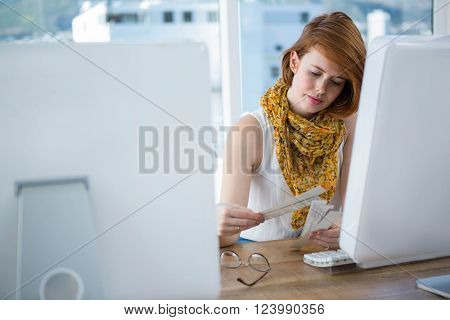 thoughtful hipster business woman sitting at her desk, browsing colour swatches