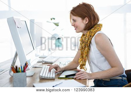 smiling hipster business woman, sitting at her desk, typing on her computer