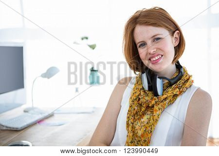 smiling hipster woman sitting at a desk, in her office, with a computer