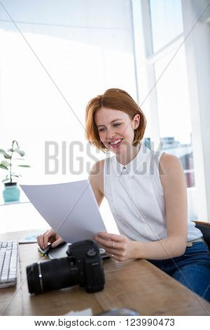 smiling hipster business woman sitting at her desk reading files