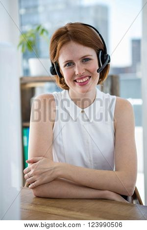 smiling hipster business woman, sitting at her desk in a wireless headset