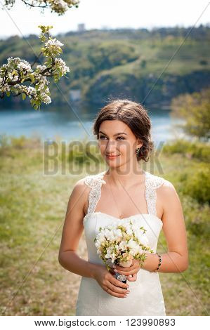 Beautiful young bride woman in luxury wedding dress with red lips makeup and long wavy hairstyle. Beauty girl portrait posing in green park outdoor photo.