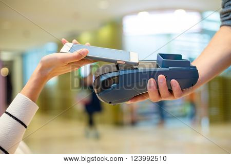 Woman paying on cellphone by NFC inside shopping mall