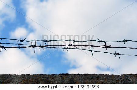 Barbed wire on top of the concrete fence with blue sky with clouds closeup