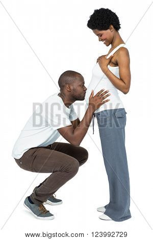 Man kissing the belly of pregnant woman on white background