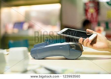 Customer paying with smartphone inside restaurant