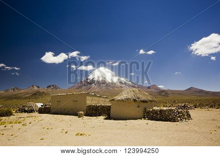 small village, several huts, in bolivia near snow covered volcano Sajama in altiplano desert