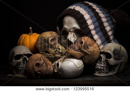 still life skulls on black background and yellow pumkin