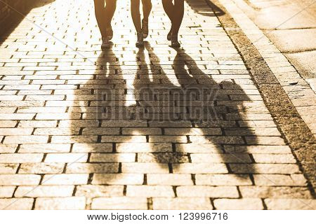 Shadows Of Three Girls Walking On A Sidewalk In The City