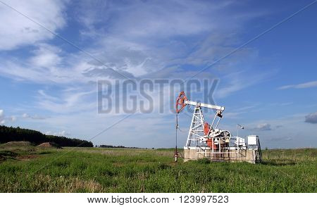 Oil pump in the field on a background cloudy sky in summer