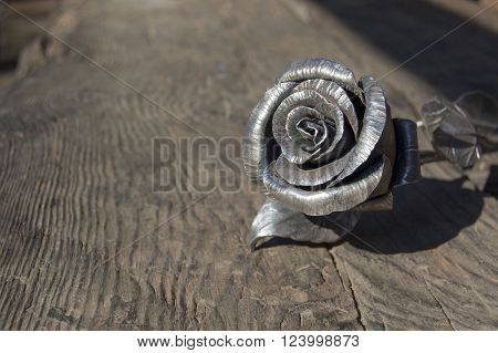 metal rose on shabby wooden background, blacksmith's work